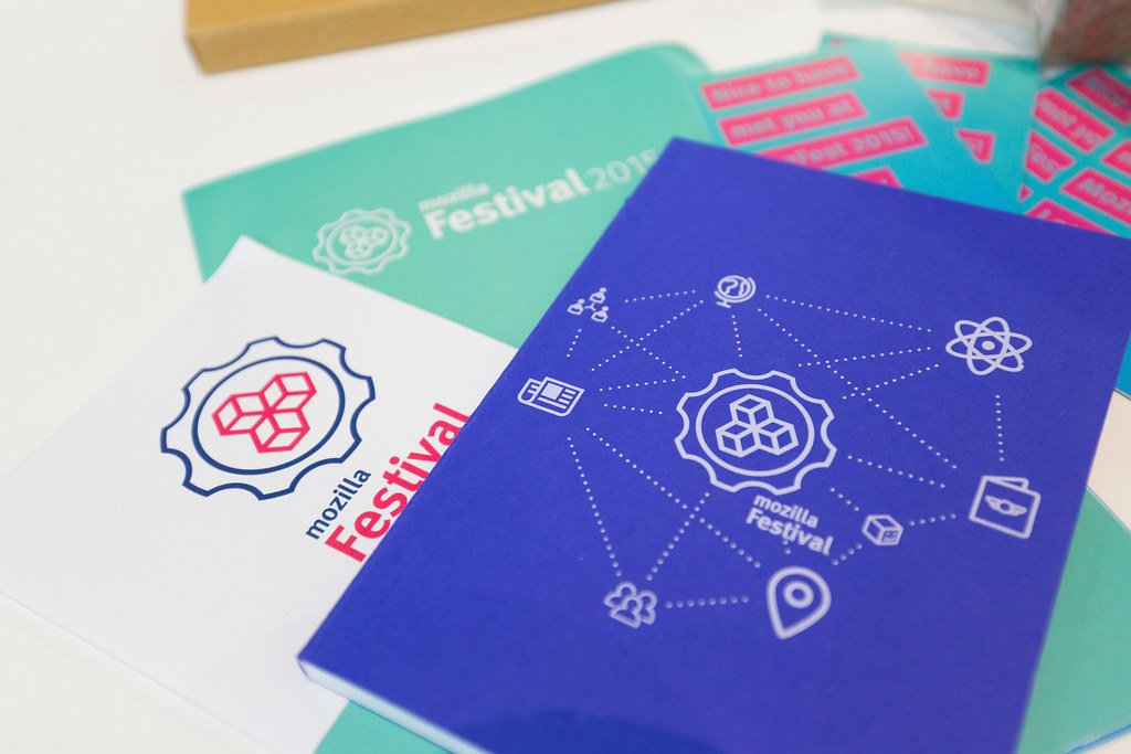 A small pile of Mozilla Festival-branded notebooks and stickers featuring the festival's gear logo sits on a white table.