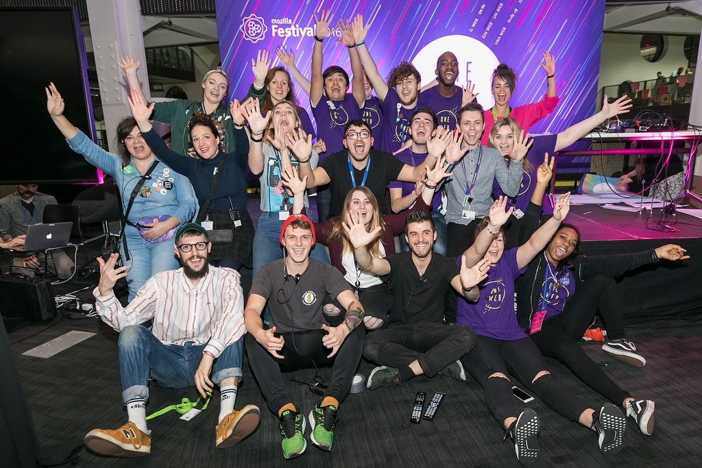 """A group of MozFest production staff and Volunteers, who are wearing t-shirts that say """"One Web"""" gather together with their arms outstretched towards the camera while cheering in front of a Mozilla Festival backdrop at MozFest 2016."""