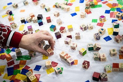 A hand reaching for a table scattered with colorful blocks