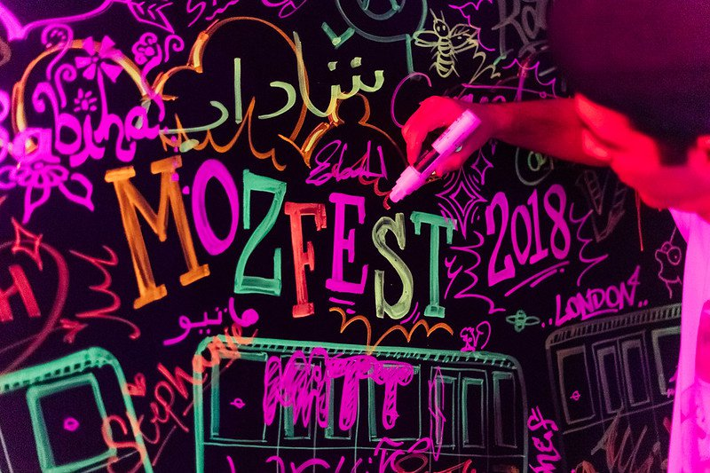 """Person writing in neon, multi-colored markers on a black board. Text says """"MozFest 2018."""""""