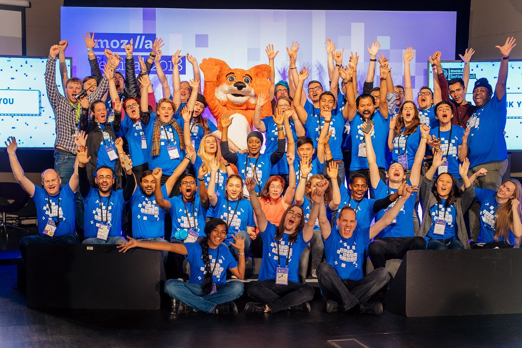 A costumed cartoon fox raises its hands in celebration while surrounded by a group of MozFest Volunteers wearing MozHelp t-shirts.