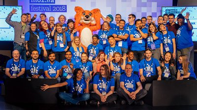 All the volunteers from MozFest 2018, standing on stage cheering.