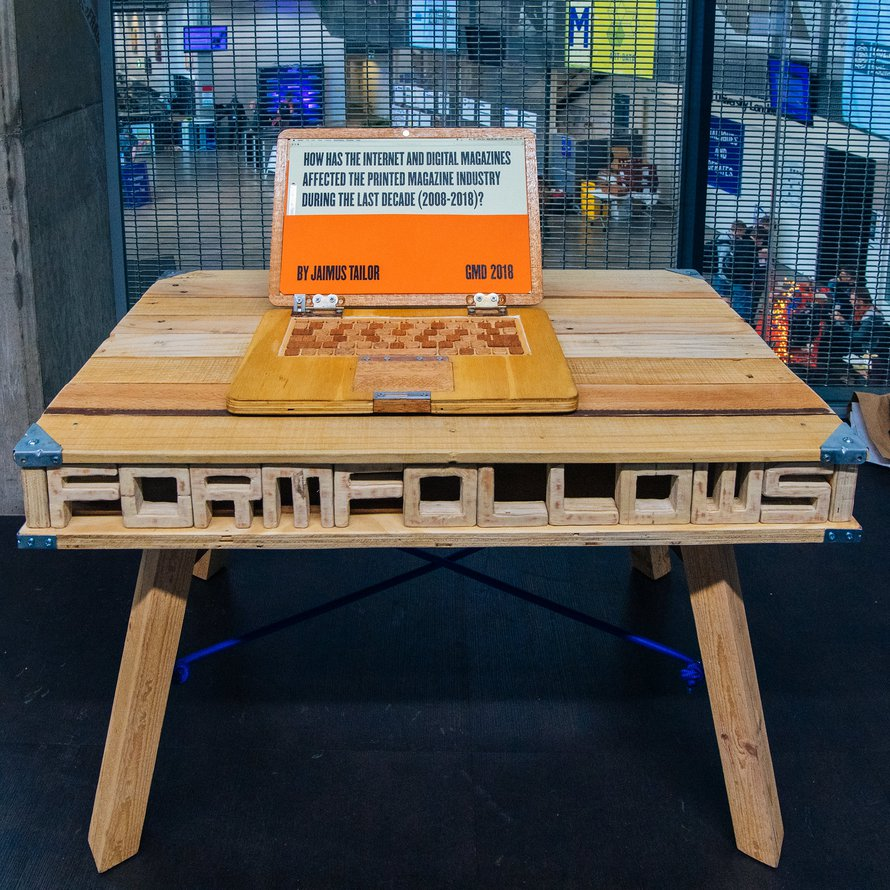 A laptop carved from wood displays the title of the artwork 'How has the internet and digital magazines affected the printed magazine in the last decade'