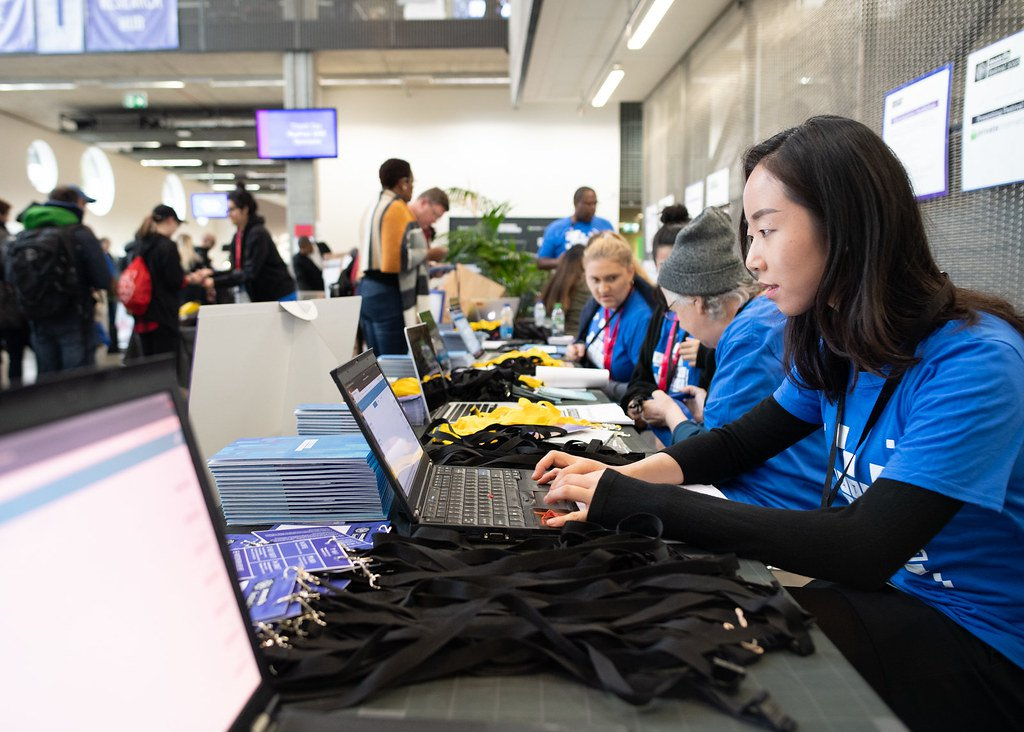 A group of MozFest volunteers in their hallmark blue t-shirts run the registration desk at MozFest 2019. They are seated  at a long table covered with lanyards, notebooks, and nametags along with a few laptop computers used for registration.