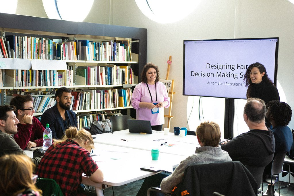 A group of MozFest attendees sit around a small conference table during a session led by two women who stand in front of a screen that displays the session's tile, 'Designing Fair Decision-Making Systems,' and there is a large bookcase in the background.
