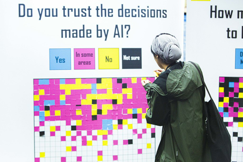 A MozFest attendee in a gray head wrap and green coat stands by a poster with a grid of sticky notes color-coded to represent whether or not AI seems trustworthy to people.