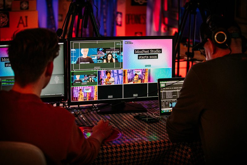 A behind the scenes photograph showing two people working with broadcast equipment, with a monitor in the middle that shows different cameras and graphics, including a presenter at a lectern, a video conference with two people side by side and a graphic that reads MozFest Studio starts soon.