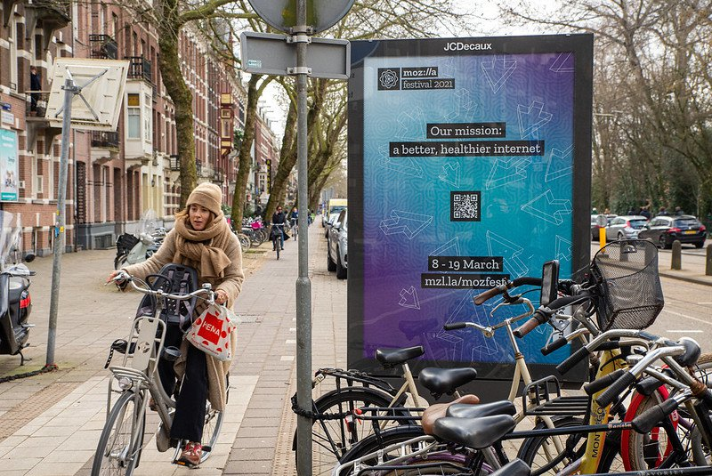 On a street in Amsterdam, digital signage announces MozFest 2021, while people on bikes zip by