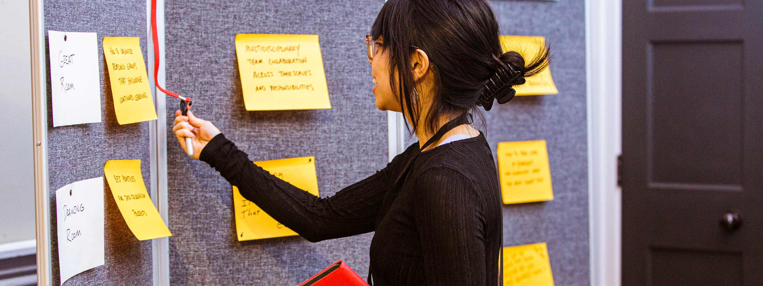 A person taking a pen off a wall and writing on sticky notes attached to the notice board