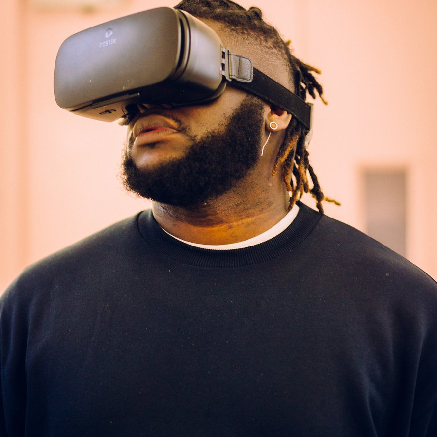 A person with a black beard wearing a VR headset and black sweater.