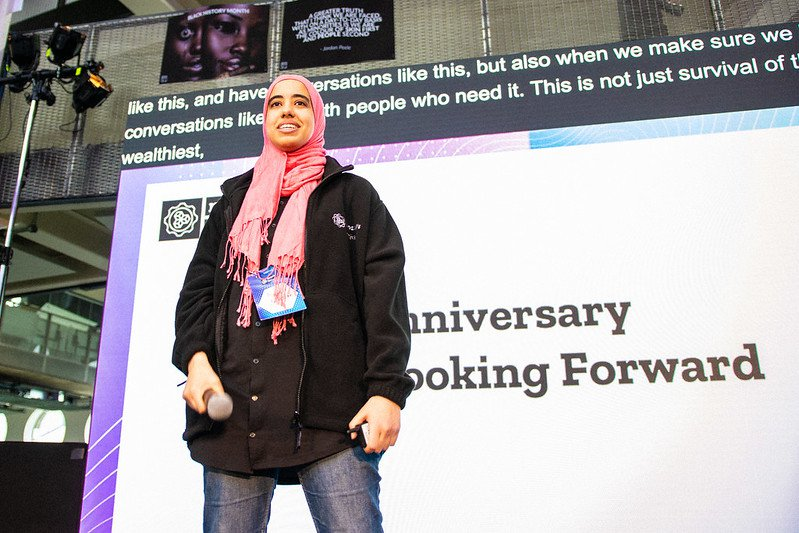 Smiling woman in pink head scarf and black jacket standing on a stage with a microphone in her hand by her side.
