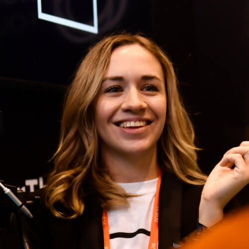 A person with medium length brown hair wearing a black and white shirt with orange accents smiling and looking off into the distance. One hand is slightly raised.
