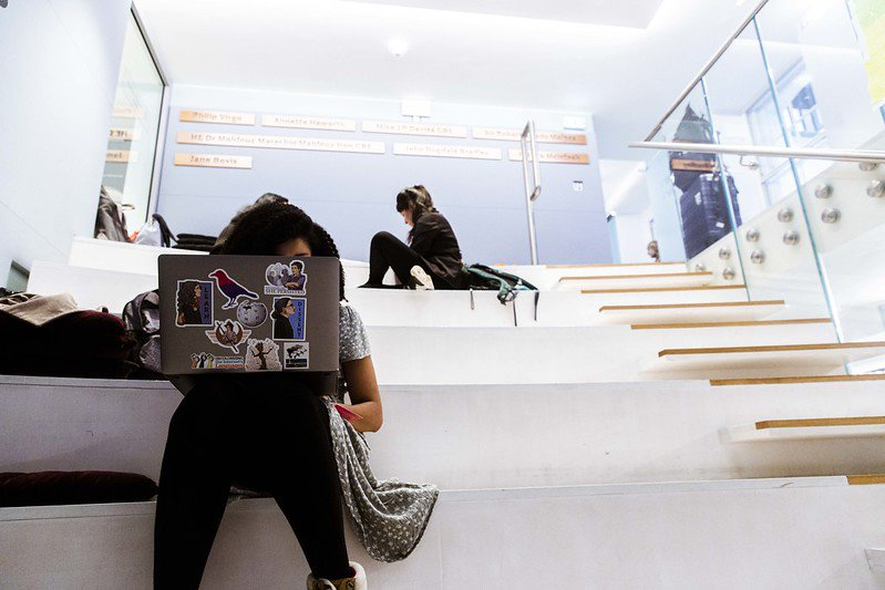 Person working on laptop sitting on stairs