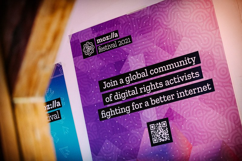 "Purple and pink poster hanging on a wall with Mozilla Festival 2021logo in the upper right corner and text ""Join a global community of digital rights activists fighting for a better internet"" and a QR code at the bottom"