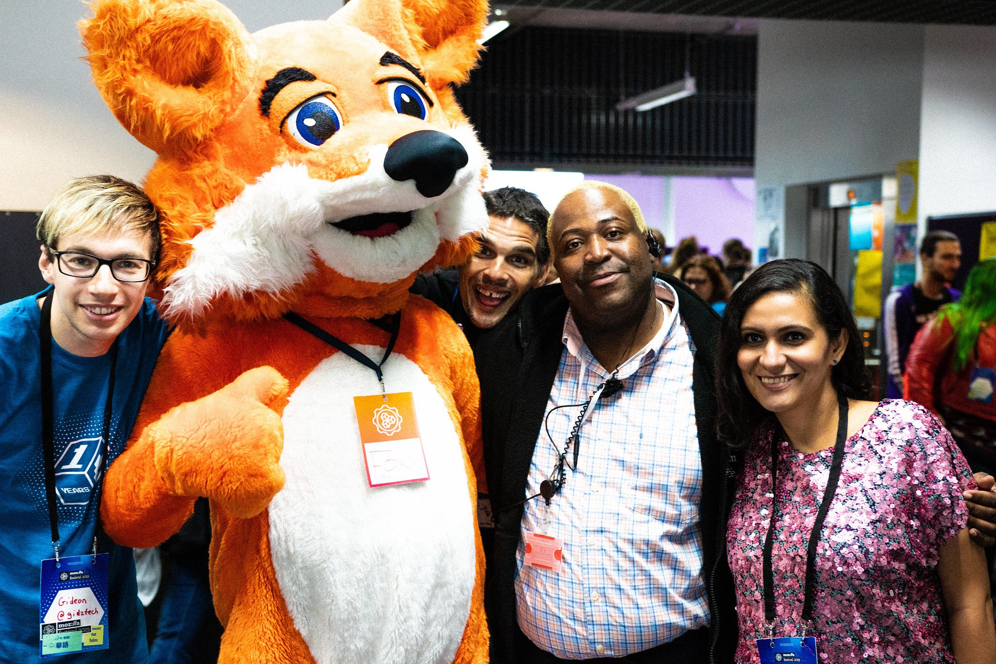 A small diverse group of people, including a person in a blue shirt (far left), a person with dark hair, a person wearing a dress shirt with a black sweater, and person with long, dark hair and a floral shirt (far right) standing together alongside a person in the Firefox mascot costume smiling at the camera at MozFest.