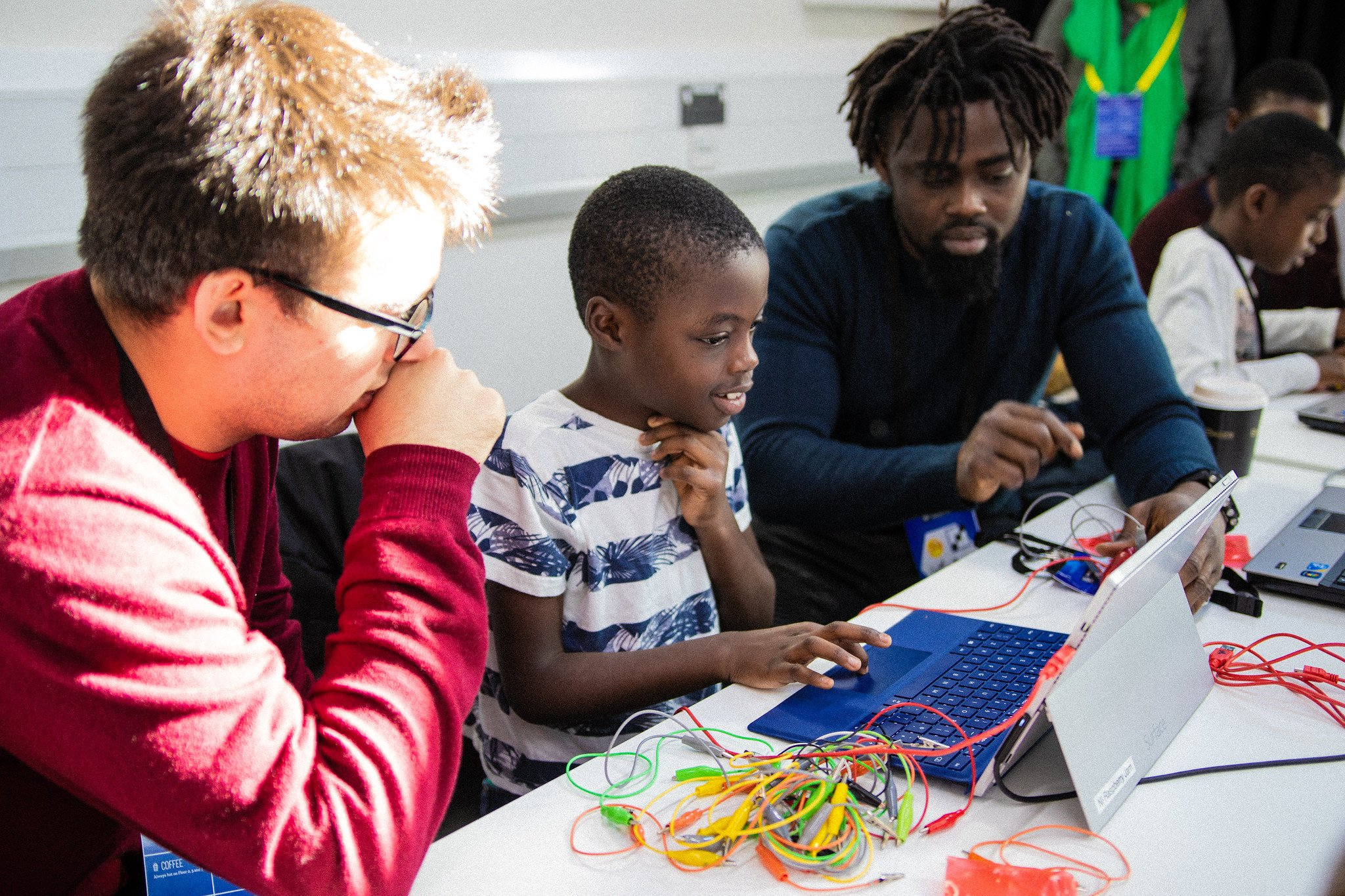 Two adults at a MozFest Youth Zone session help a young participant work on a computer project.