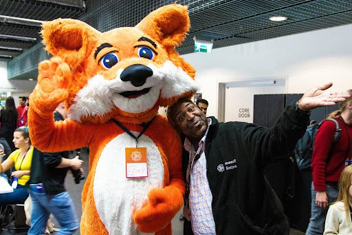 Person in large furry fox suit stands next to man in black Mozilla Festival fleece jacket.  Both are waving to the camera.