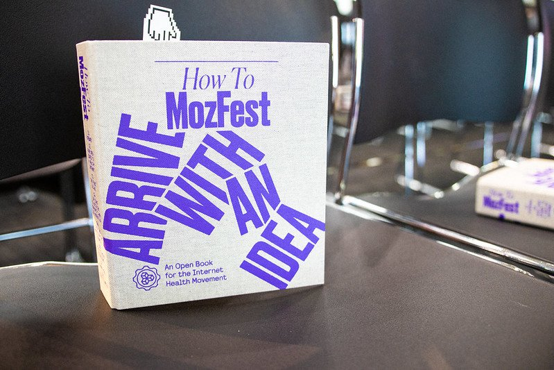 """A photo of a book sitting upright on a chair. Cover reads """"How To MozFest Arrive With An Idea"""""""