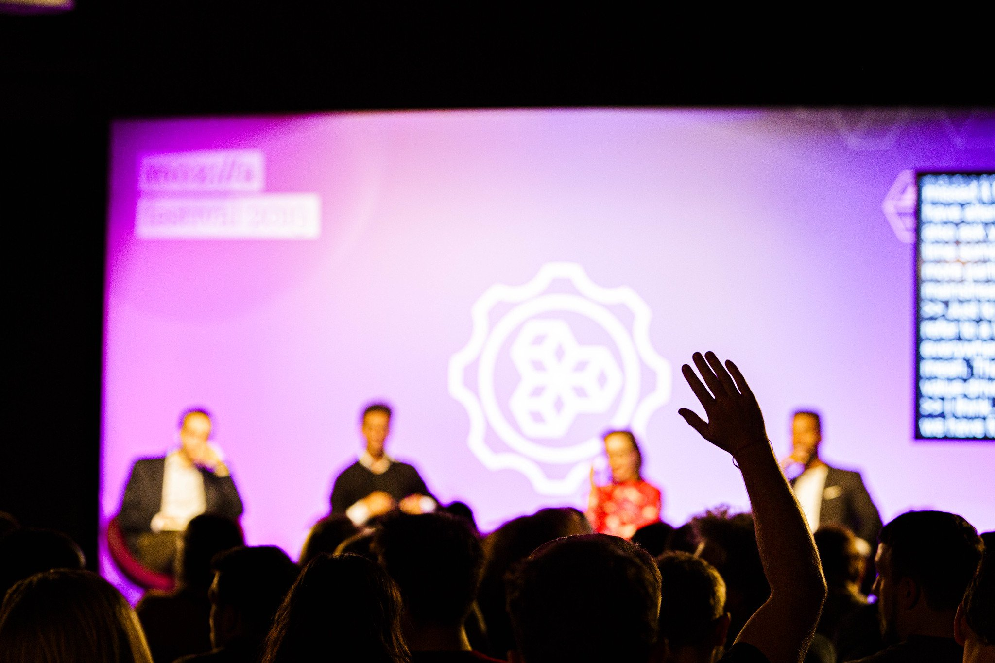 A panel of four speakers on stage in the background, with a person raising their hand in the foreground.