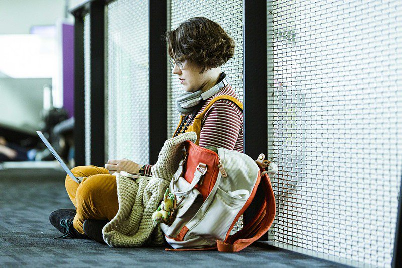Person with short curly hair sitting against a wall with laptop in their lap and backpack beside them.