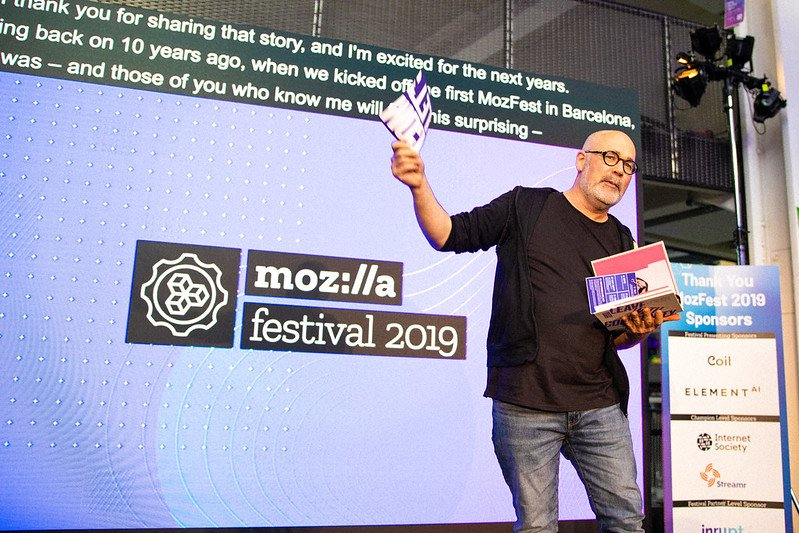 Person in black shirt and jeans holding up MozFest book, with festival sponsor's logos on a banner in the background.