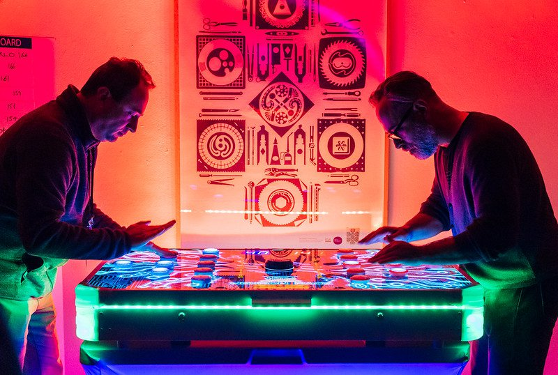 Two people playing a game lite up by neon and black lights.