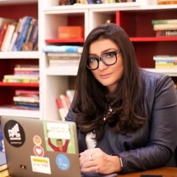 Person with long, dark hair and dark rimmed glasses leaning against a desk with a laptop open, looking at the camera.