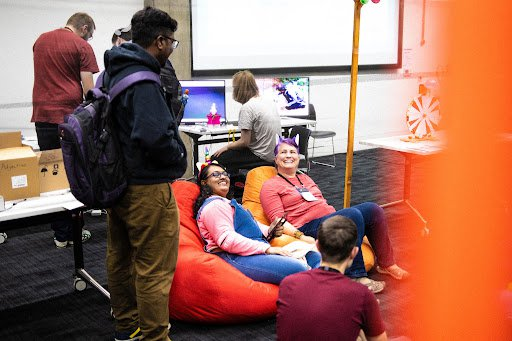 A group of people smiling and talking, some standing, some sitting in bean bags.