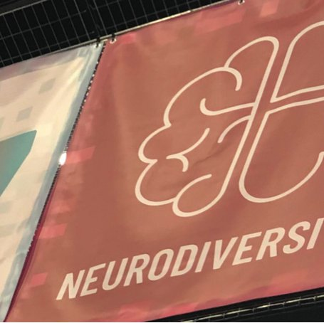The Neurodiversity logo (of a brain made half of love hearts) is on a banner hanging next to the banner for the 7th floor.