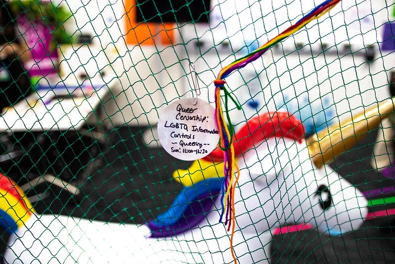 Queering MozFest Session Note on netting that hangs above unicorn blowup | Digital Inclusion work
