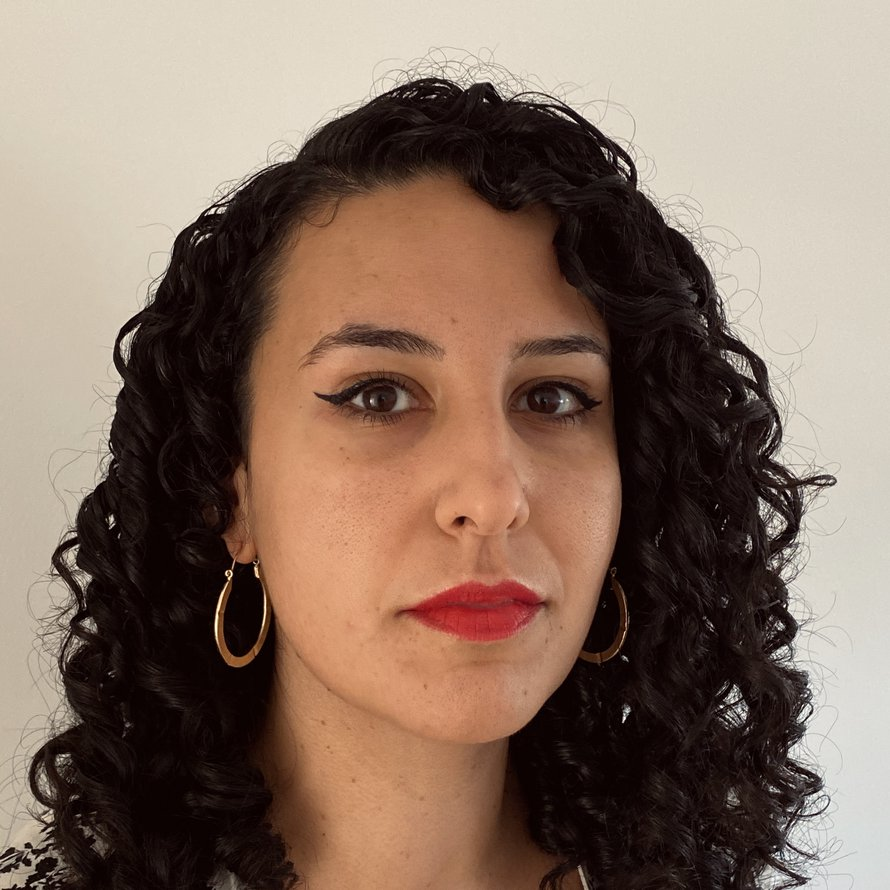 A person with dark curly hair, wearing hoop earrings and a collared shirt looking at the camera