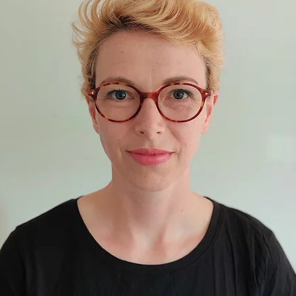A person with short blond hair wearing red rimmed glassed and a black shirt looking at the camera