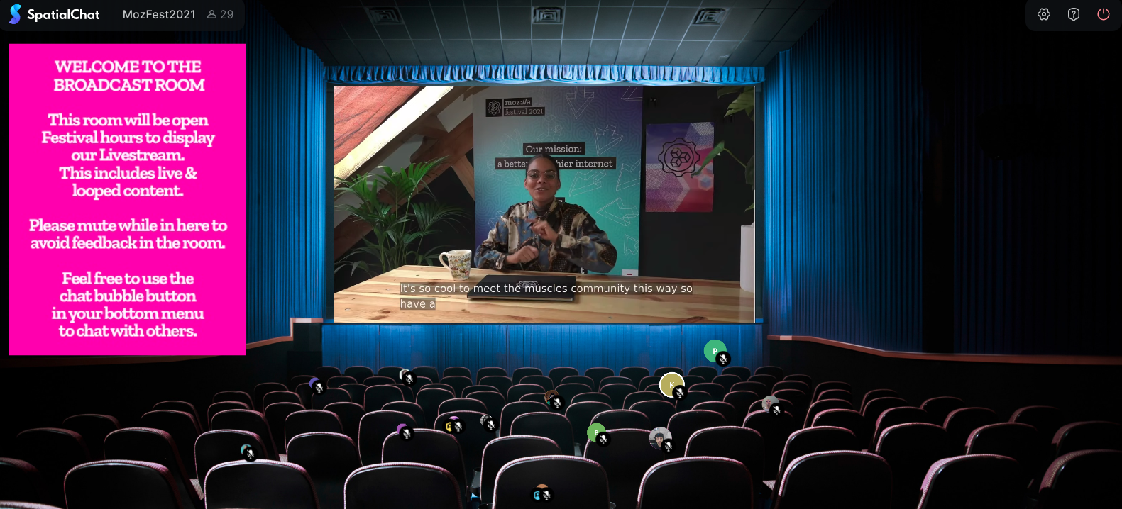 Virtual room that looks like a movie theater with a person on the big screen. A pink box is on the left hand side with instructions on how to use the room.