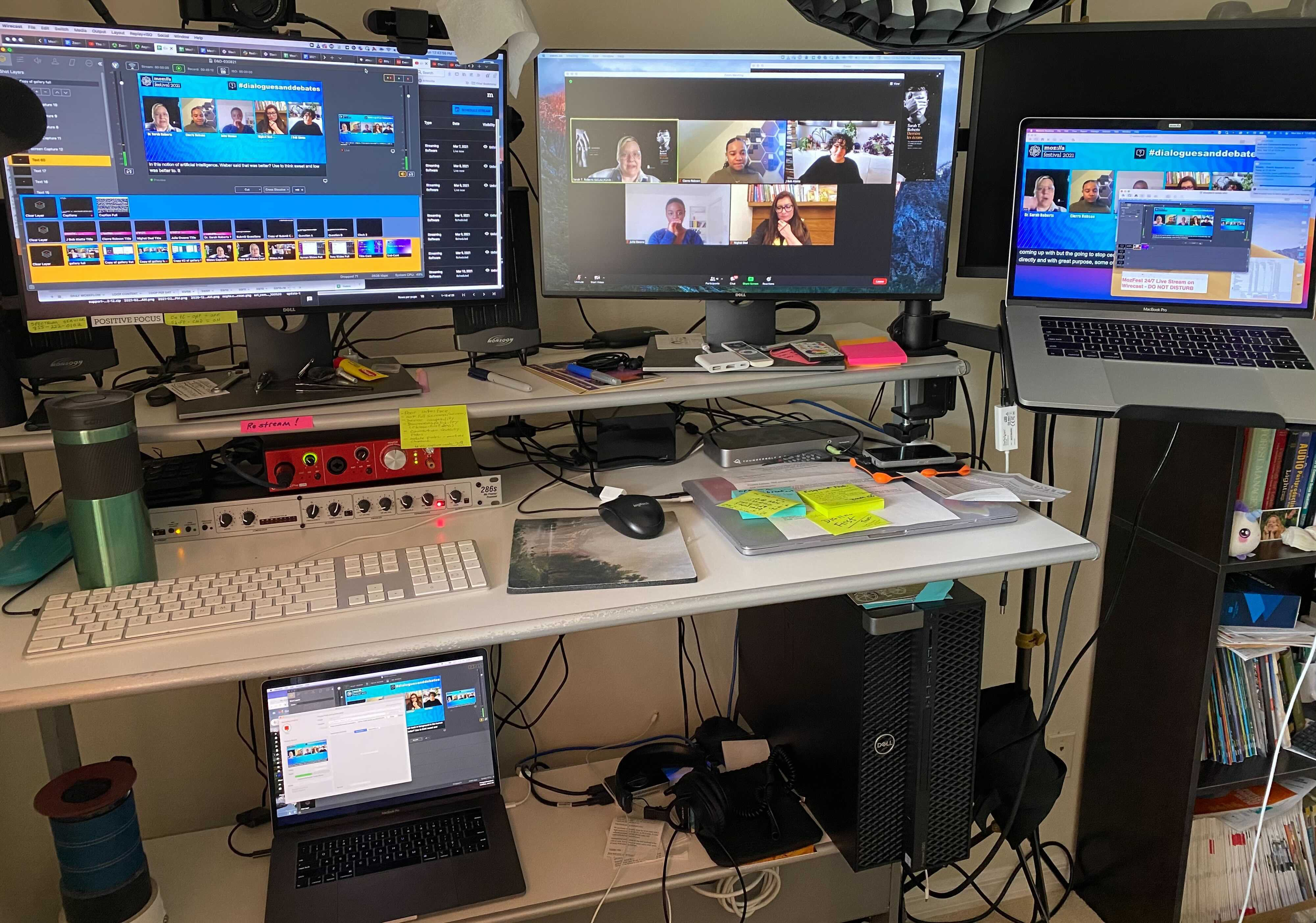 Live stream A/V workstation with multiple monitors on top of and below desk showing various views of the behind the scenes of a live broadcast