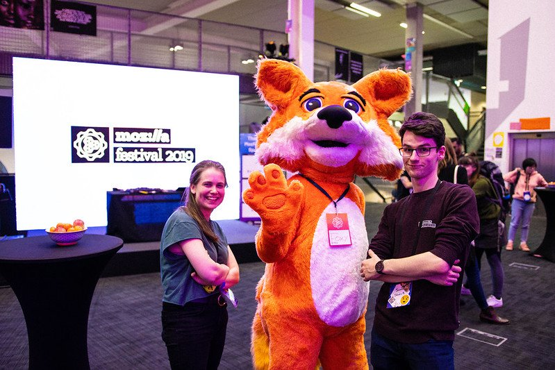 Three figures standing in front of a screen with the MozFest 2019 logo: a woman on the left, Mozilla's Foxy mascot in the middle, and a man on the right.