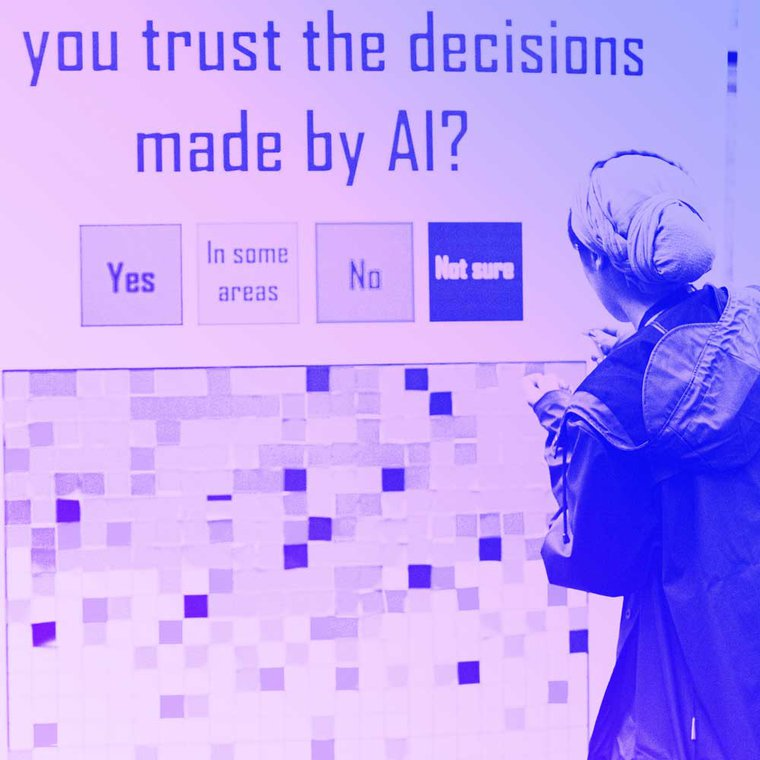 A person stands by an installation at MozFest with the title 'Would you trust decisions made by AI' with people adding red, yellow and green stickers depending on their level of trust.