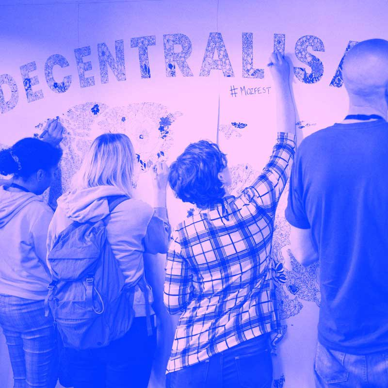 Group of participants at MozFest colouring in decentralisation poster