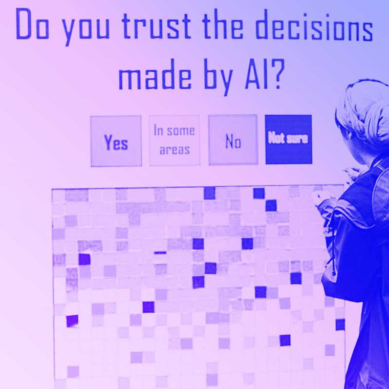 A person stands in front of an installation at MozFest where people place a sticky note of a certain color depending if they agree with the statement Do you trust the decisions made by AI