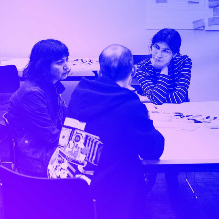 A group of three MozFest participants sit around a table in discussion.