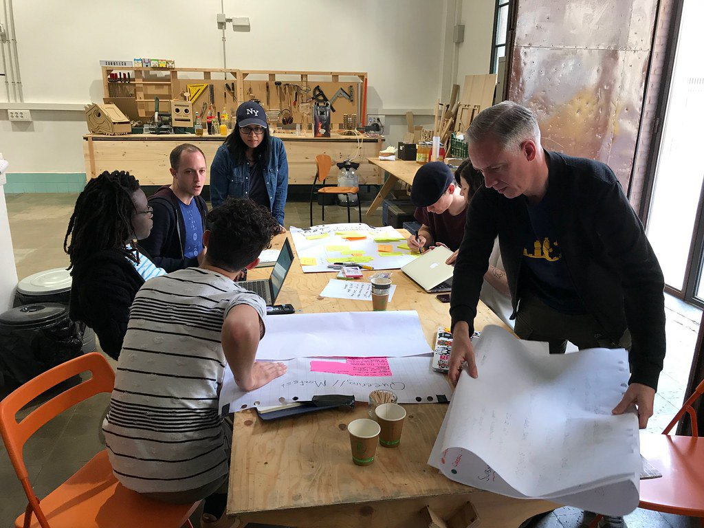 A group of seven people in casual dress have a lively discussion about planning MozFest while sitting around a wooden table covered with sticky notes, markers, laptops, and coffee cups inside of an industrial workshop space with tool benches in the background.