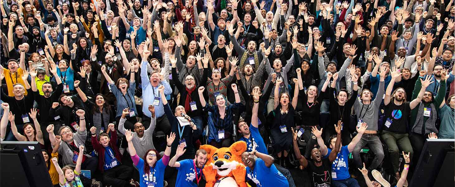 A large group of people are sat together cheering with their hands up in the air, in the center at the bottom of image is an orange fox mascot.