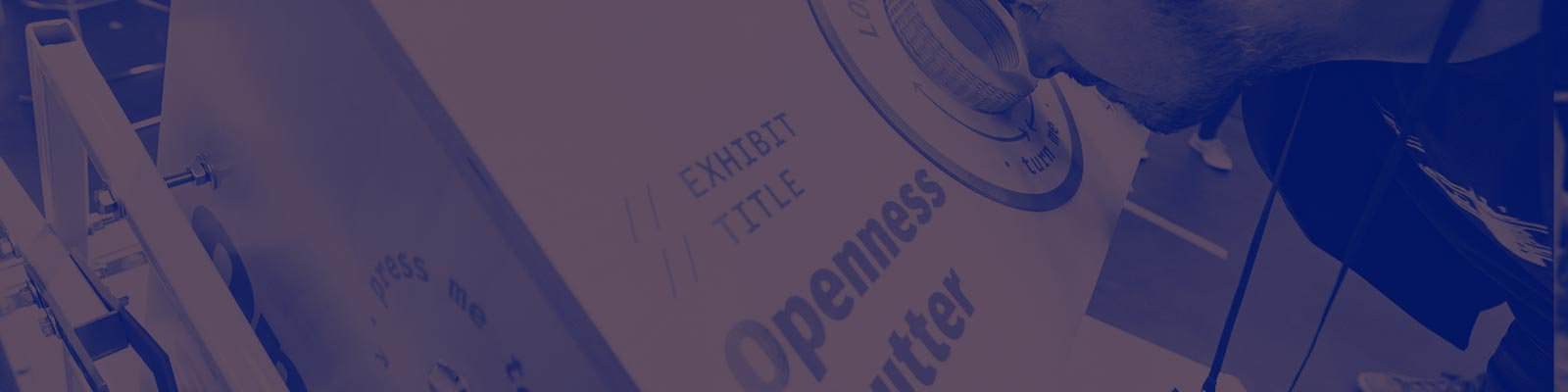 A person stands at an installation looking into a lens. The title of the installation is printing onto the side and reads 'Openness Shutter'