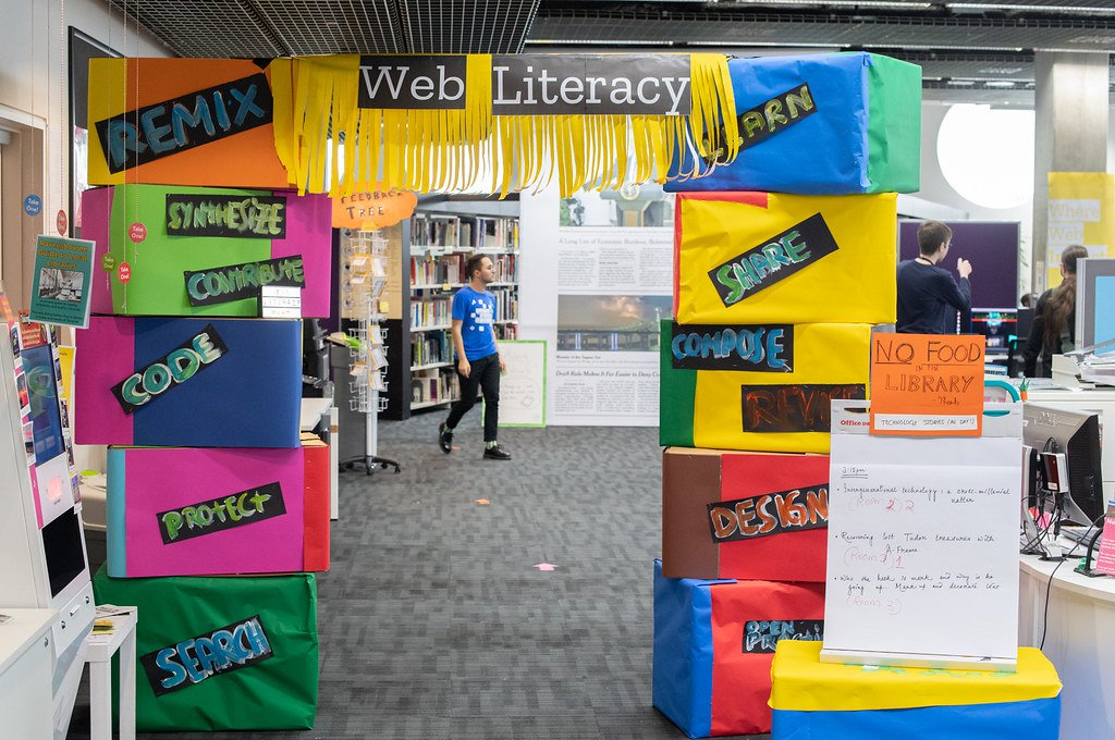 "An image of cardboard boxes stacked and stuck together to make a squared arch with each box covered in brightly colored construction paper a signs with words like, ""Web Literacy,"" ""Learn,"" and ""Remix."""