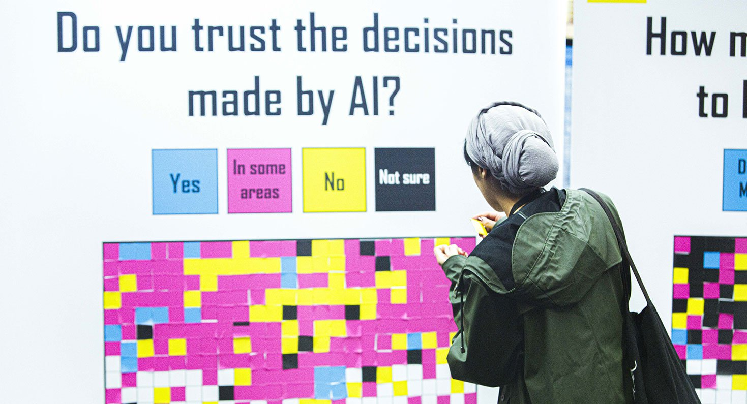 Een persoon voor een groot paneel vol notitieblaadjes, waarop staat 'do you trust the decisions made by AI?'